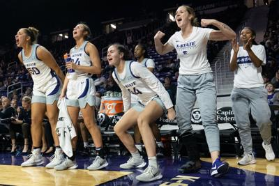 The K-State womenÕs basketball team bench celebrates after their teammate scored.