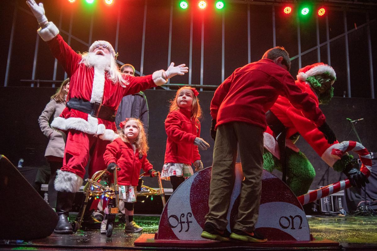 Santa Clause, Faith Herrman, Lydia Herrman, Silas Hermann and the Grinch flip the switch