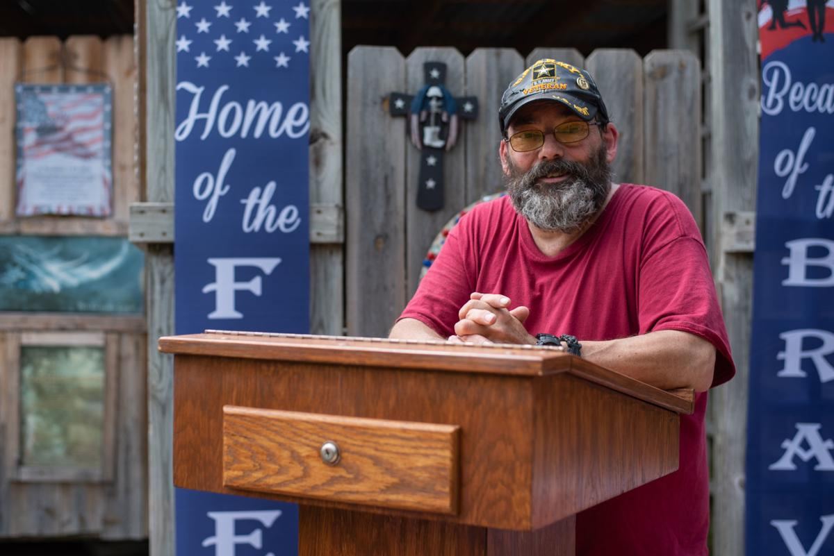 Chris Dunham stands in his front yard where he created the Pathway and Memorial of Honor as a way to honor those who served in uniform and the battles they fought to protect America's freedoms.