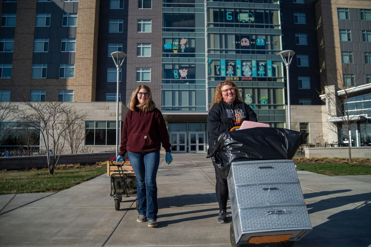 Kelsie Rehkop, left, and Krista Rehkop, right, walk out of Wefald Hall with Katie RehkopÕs belongings during her move-out slot on Friday.