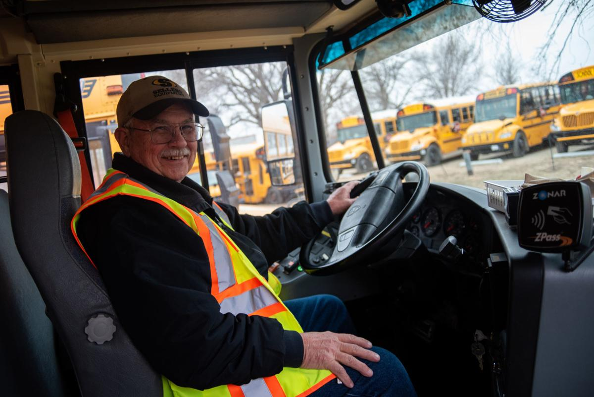 Dale Hayden sits in the driver's seat of his school bus while in the parking lot at the USD 383 Transportation Department.