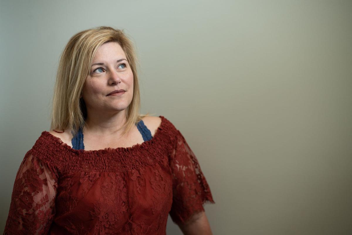 Lisa Julian, a teacher at Manhattan High School, stands in her home on Wednesday.