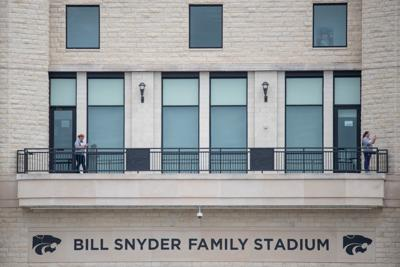 Two people stand on the balcony at Bill Snyder Family Stadium before the National GuardÕs 190th Air Refueling Wing flies over Ascension Via Christi Hospital at 1:13 p.m. on Tuesday.