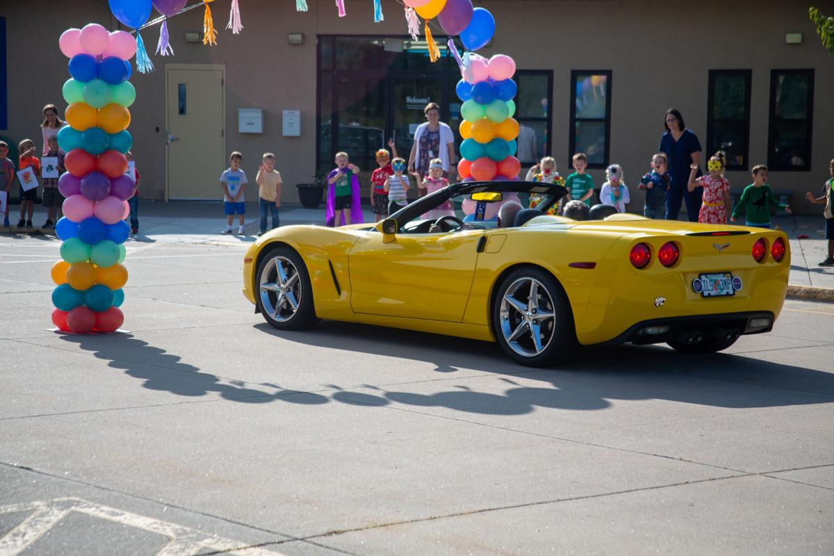A yellow convertible celebrates in style waving at kids as they go by. Grandparents day celebrates in a safe way by waving from cars to their grandchildren.