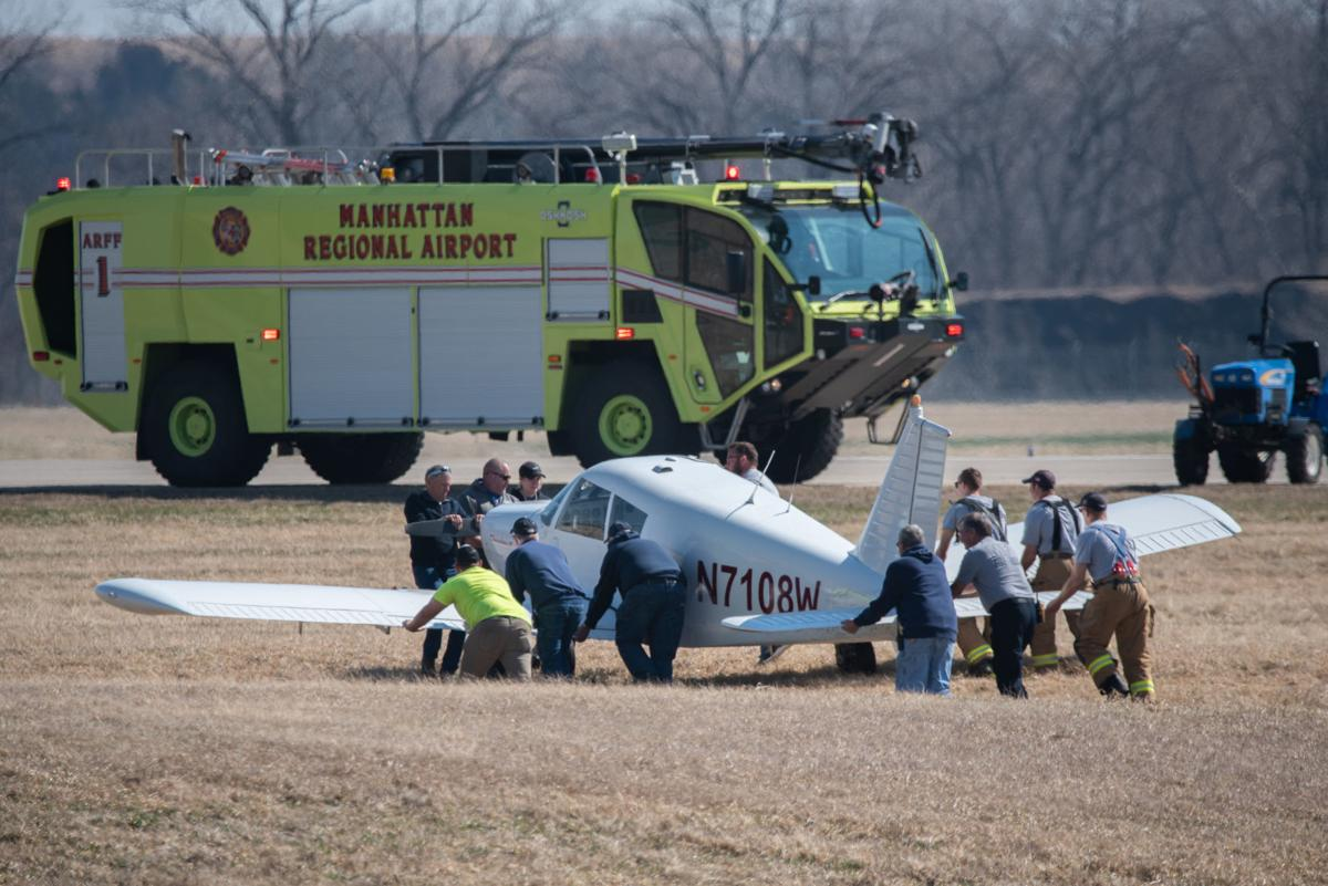 Firefighters and airport staff push an airplane out of the grass and onto the runway at Manhattan Regional Airport.