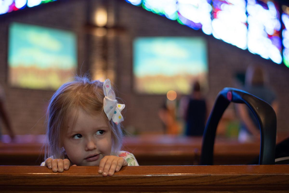 Victoria Allgeyer, 3, peeks over the church pew during worship at Peace Lutheran Church on Sunday.