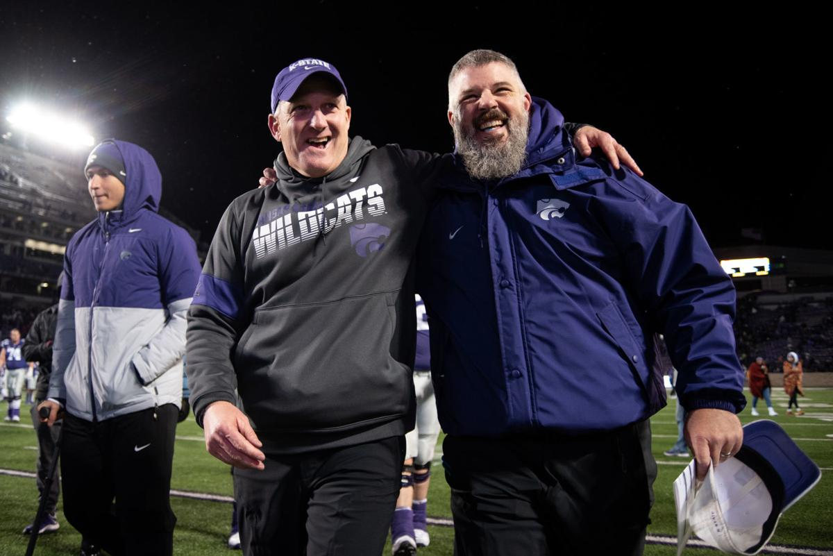 K-State head coach Chris Klieman and K-State defensive coordinator Scottie Hazelton walk off the field embracing one another