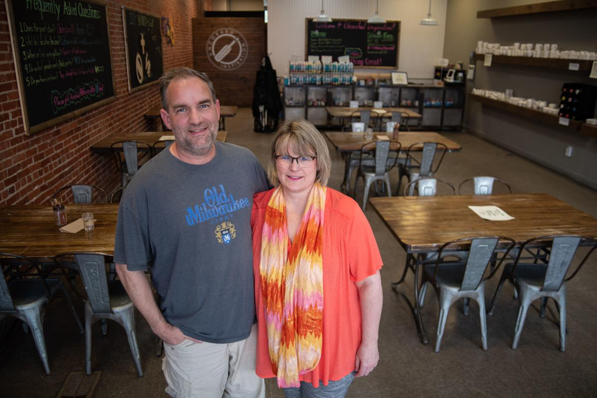 Andrea and Neal Wollenberg stand inside their business in Aggieville, Uncorked Inspiration.