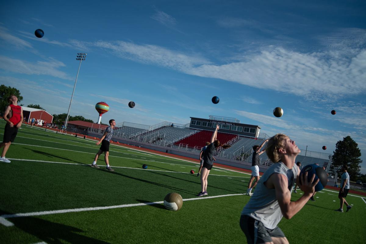 Wamego High athletes throw medicine balls in the air during their workout on Monday morning.