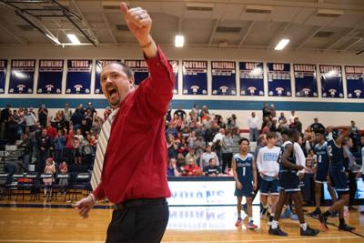 Manhattan head coach Benji George gives a thumbs up to the student section after defeating Wichita East.