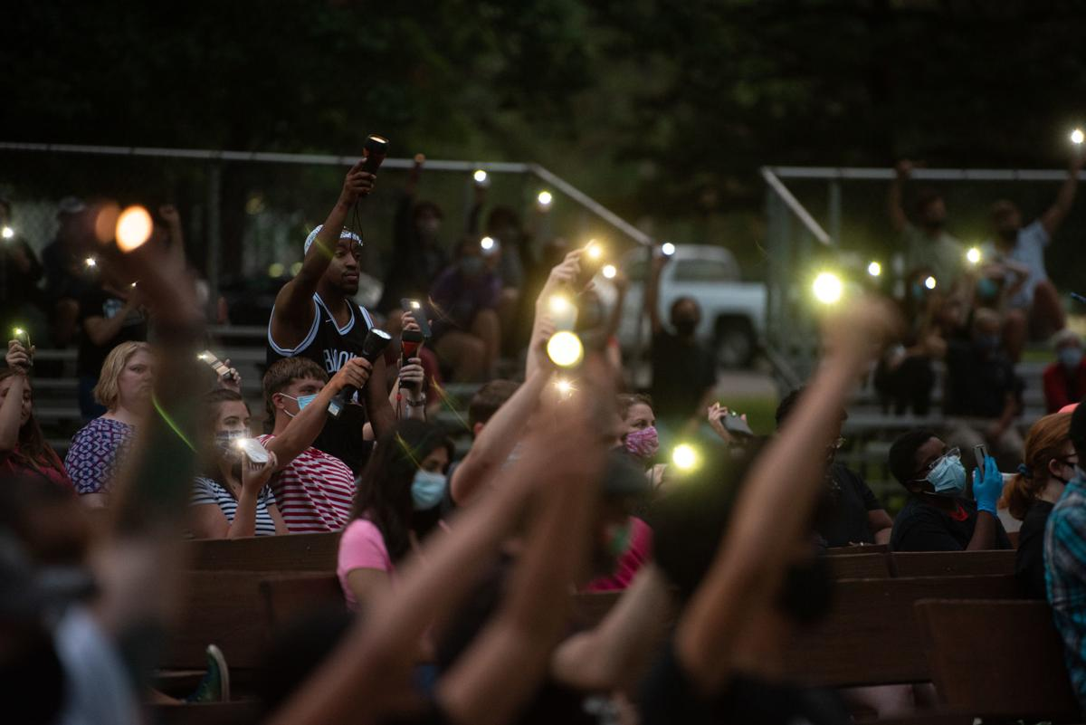Sterling Muse holds his flashlight in the air with fellow peaceful protestors for 8 minutes and 46 seconds at Wefald Pavilion during the Flashlight Vigil on Friday.