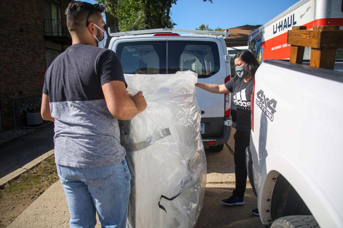 Miguel Perez (left) lifts mattress with Judith Perez (right) during move in on Saturday. The first week of August is when many college students move into their homes for the semester.