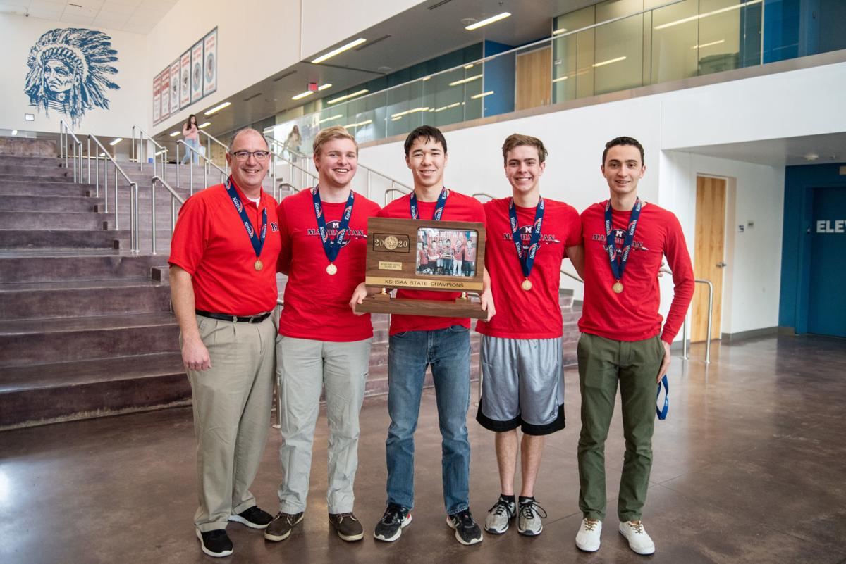 From left, Scholars Bowl head coach Ted Dawdy, Josh Brandt, Brian Dudely, Ethan Myer and Alejandro Ortiz stand in the entrance of Manhattan High School with their Scholars Bowl 6A Championship Trophy.