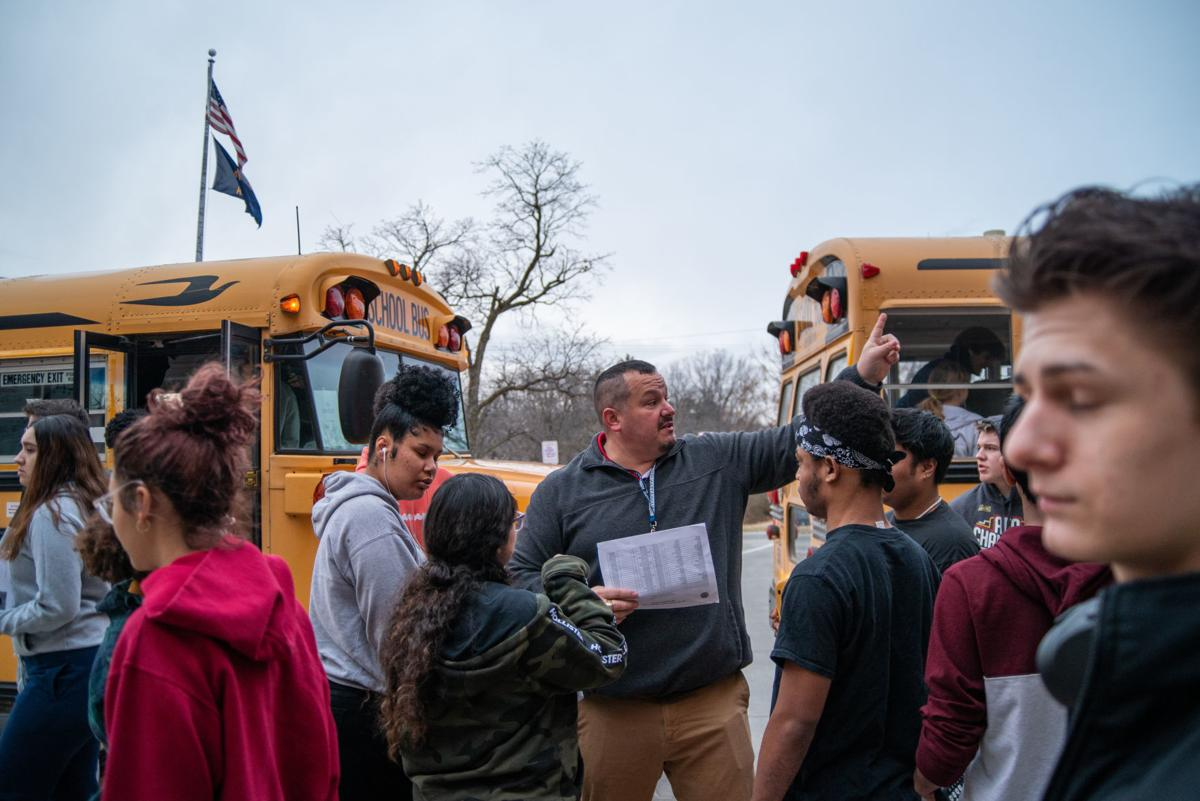 Ben Jimenez, Manhattan High 11th Grade Assistant Principal, helps students find the correct bus to get on for ACT testing.
