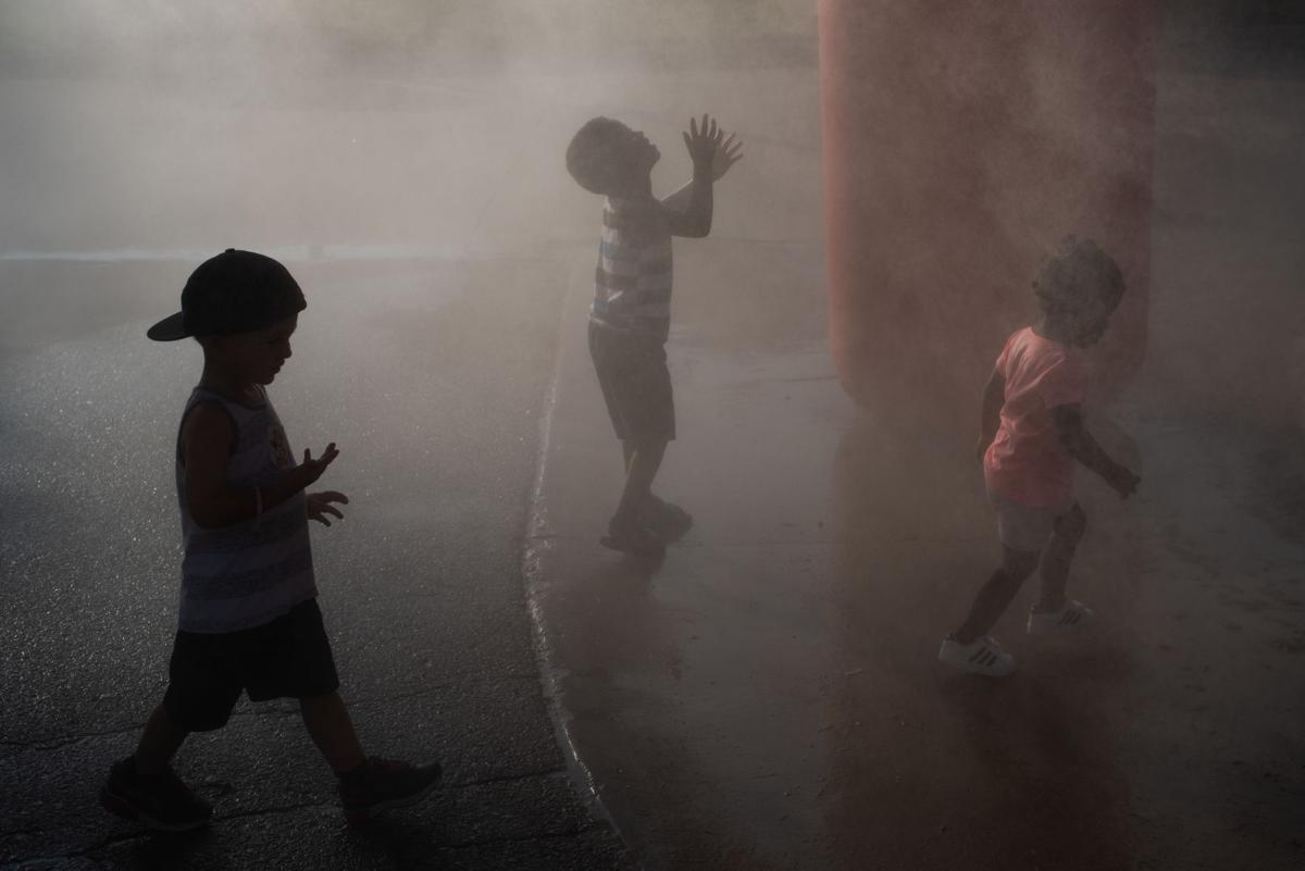 From left, Connor Little (2), accompanied by his mother Hillary Little, Nedemiah Skillern (4) and Nova Scott (2), accompanied by their mother April Self, walks through the mist tent at Purple Power Play in City Park on Thursday.