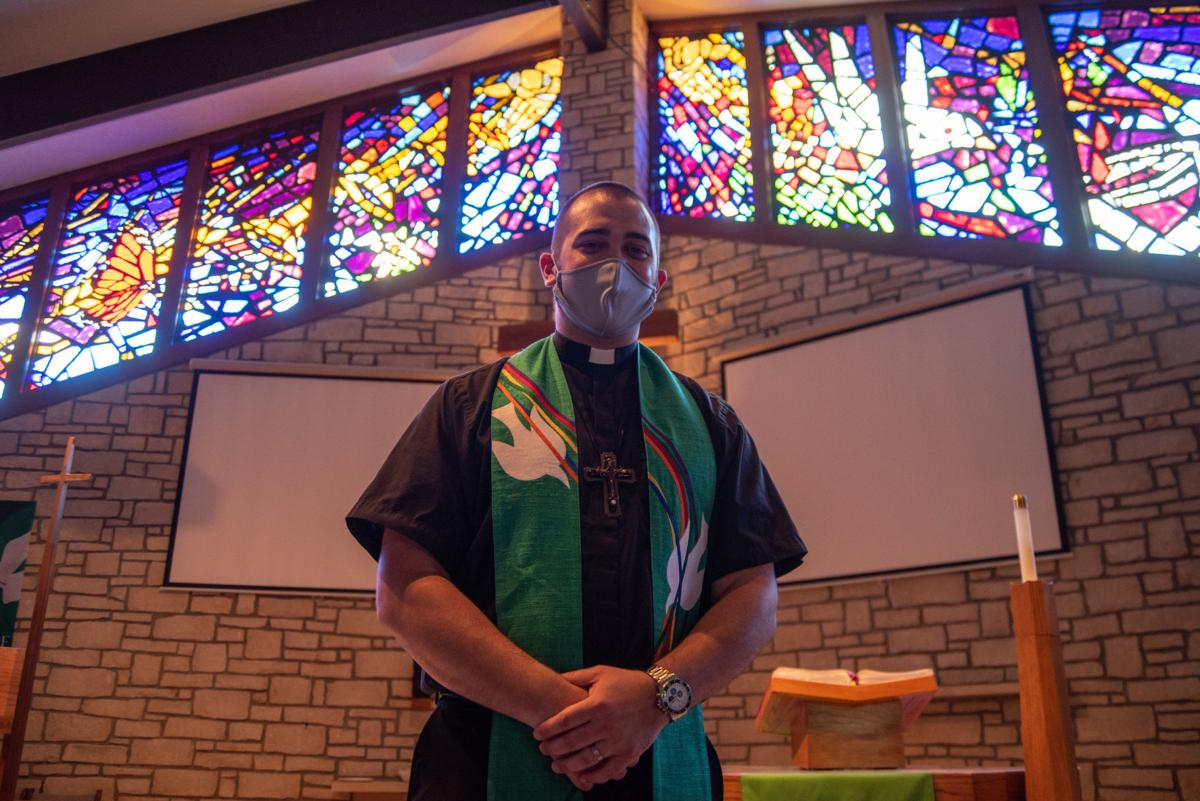 Pastor Austin English stands in front of the altar and stained glass windows, made by Maury Berggren, after SundayÕs service at Peace Lutheran Church.