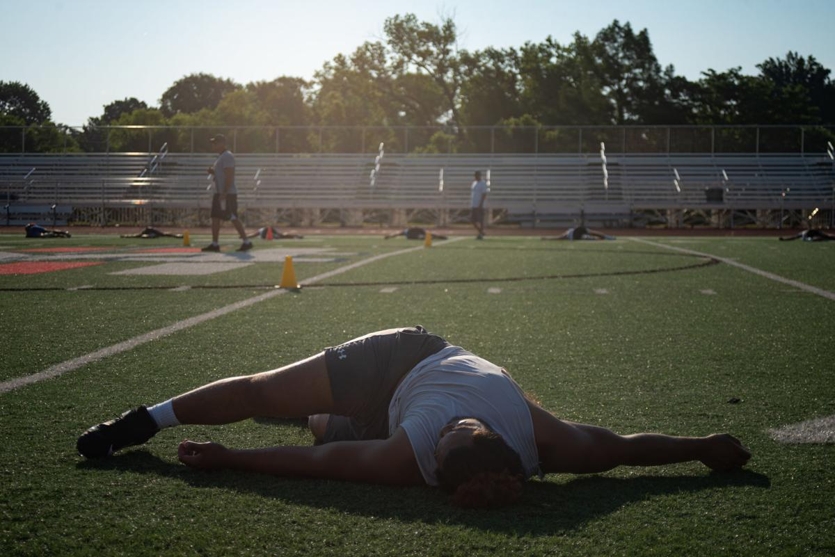 Damian Ilalio stretches during summer training with fellow Manhattan High athletes at Bishop Stadium on Tuesday morning.