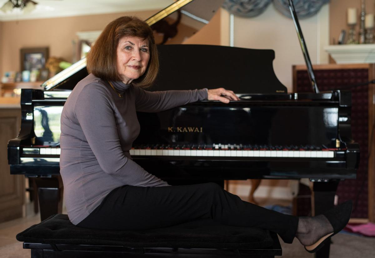 Jan Barkey sits next to her Kawai Grand Piano in her home on Saturday morning.