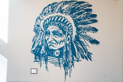 The Manhattan High logo of an Indian is on the wall in the entrance of Manhattan High School.