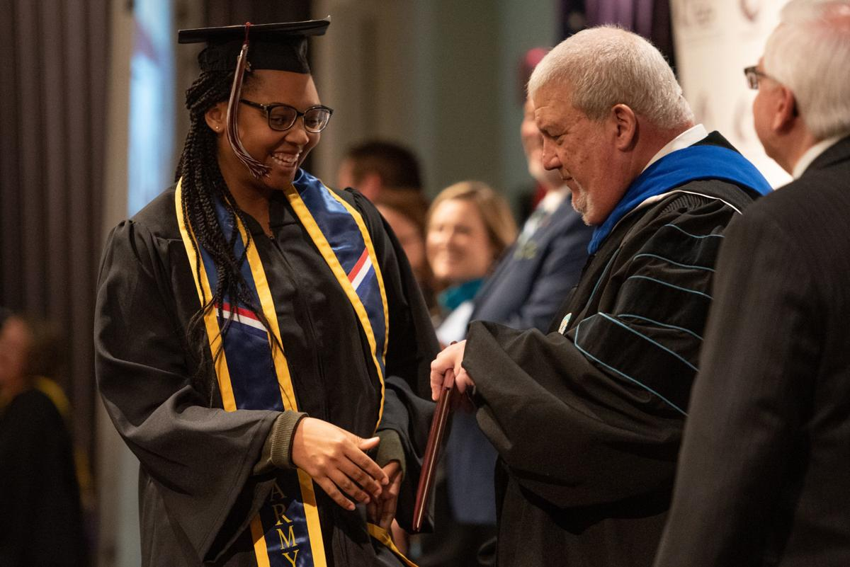 Kesha Beaufosse is handed her degree by James Genandt on stage during the fall commencement ceremony.