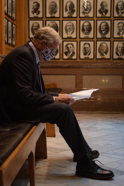 K-State President Richard Myers reads over his notes before presenting Dennis Ruhnke his college degree from K-State University at the Kansas State Capitol in Topeka.