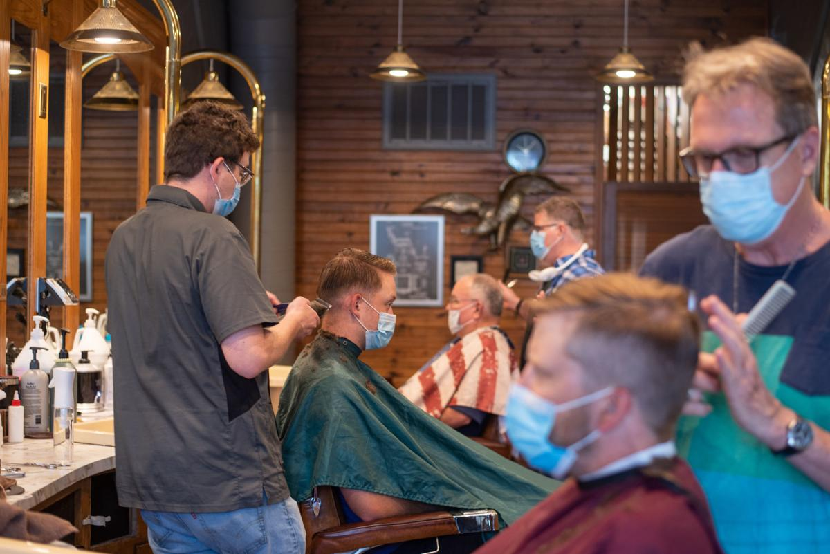From the front, Randy Sievers cuts Adrian BakerÕs hair, Dylan Roberts cuts Jackson HermsÕ hair and Bryan Burrows cuts Jim Pitts hair at Campus Barbershop on Wednesday.
