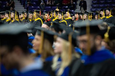 Graduate students sit patiently and wait to be called on stage.