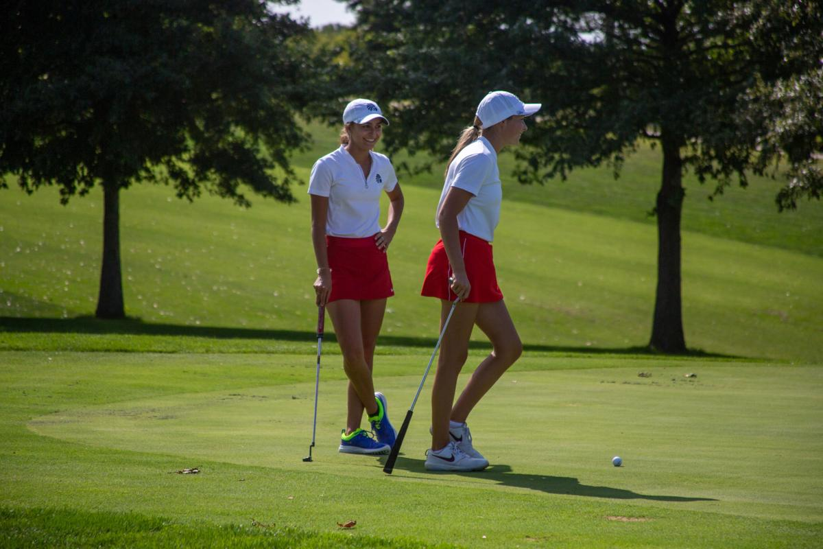 Andi Siebert smiles at Rhys Phipps who goes to swing. The woman's golf teams played Monday at the Manhattan Country Club.