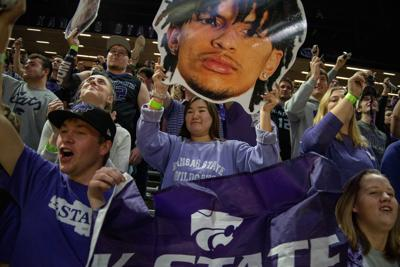 A K-State student holds up a cut-out of Mike McGuirl.