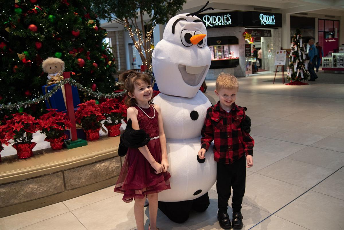 Kayla Reyes, 5, and Wyatt Reyes, 4, get their photo taken with Snowlaf