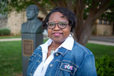 Patricia Hudgins, associate director of the K-State Career Center, smiles close to the MLK statue outside Ahearn.