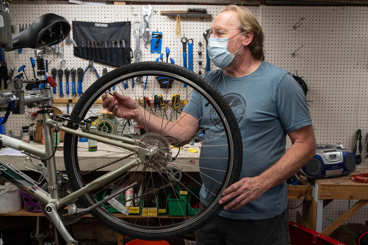 Dave Colburn, manager for 30 years at Pathfinder, fixes a bike at Pathfinder on Wednesday.