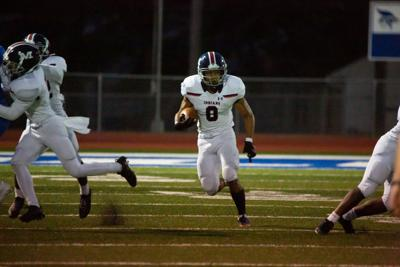 Running back Vincent Smith, junior, is in a clearing made by his teammates. Manhattan High Indians went head to head against the Junction City Bluejays on Friday night at Al Simpler Stadium with a final score of Junction City 36, Manhattan 29.