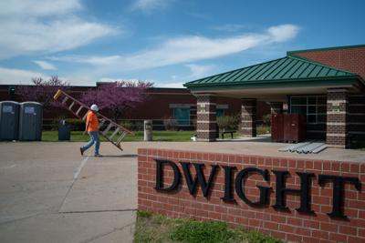 A construction worker carries a ladder into Dwight D. Eisenhower Middle School.