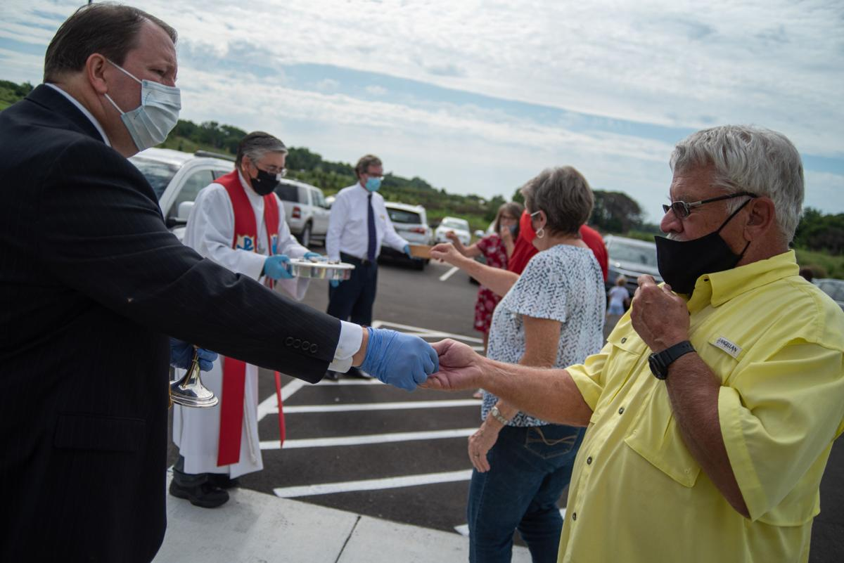 Church-goers who watched or listened to their service from their vehicle partake in communion outside the church during the service of dedication at St. LukeÕs Lutheran Church on Sunday.