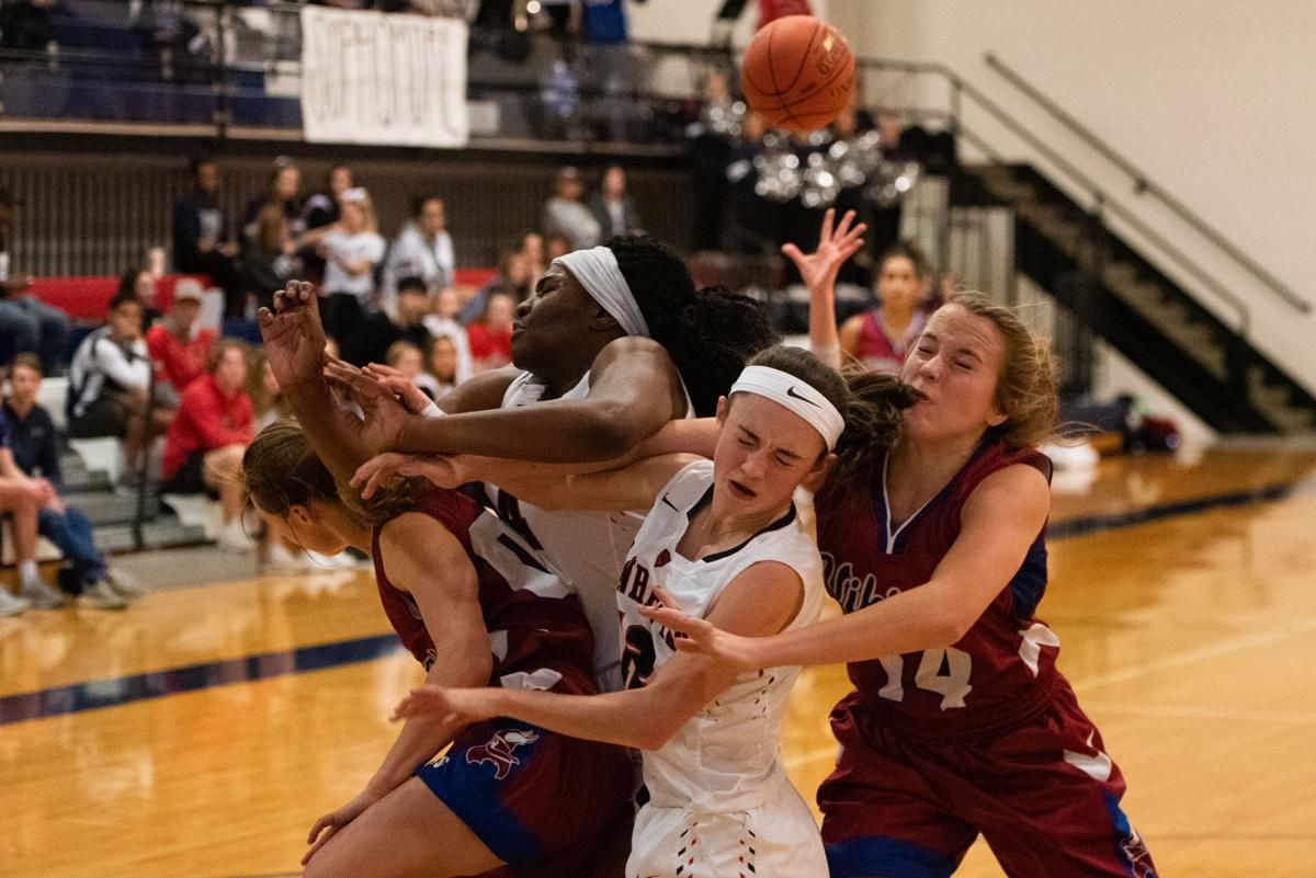 Raigan Kramer (00), Zanaa Cordis (44), Amellia Knopp (12) and Riley Cowan (14) run into one another under the hoop after Knopp attempted a lay-up.