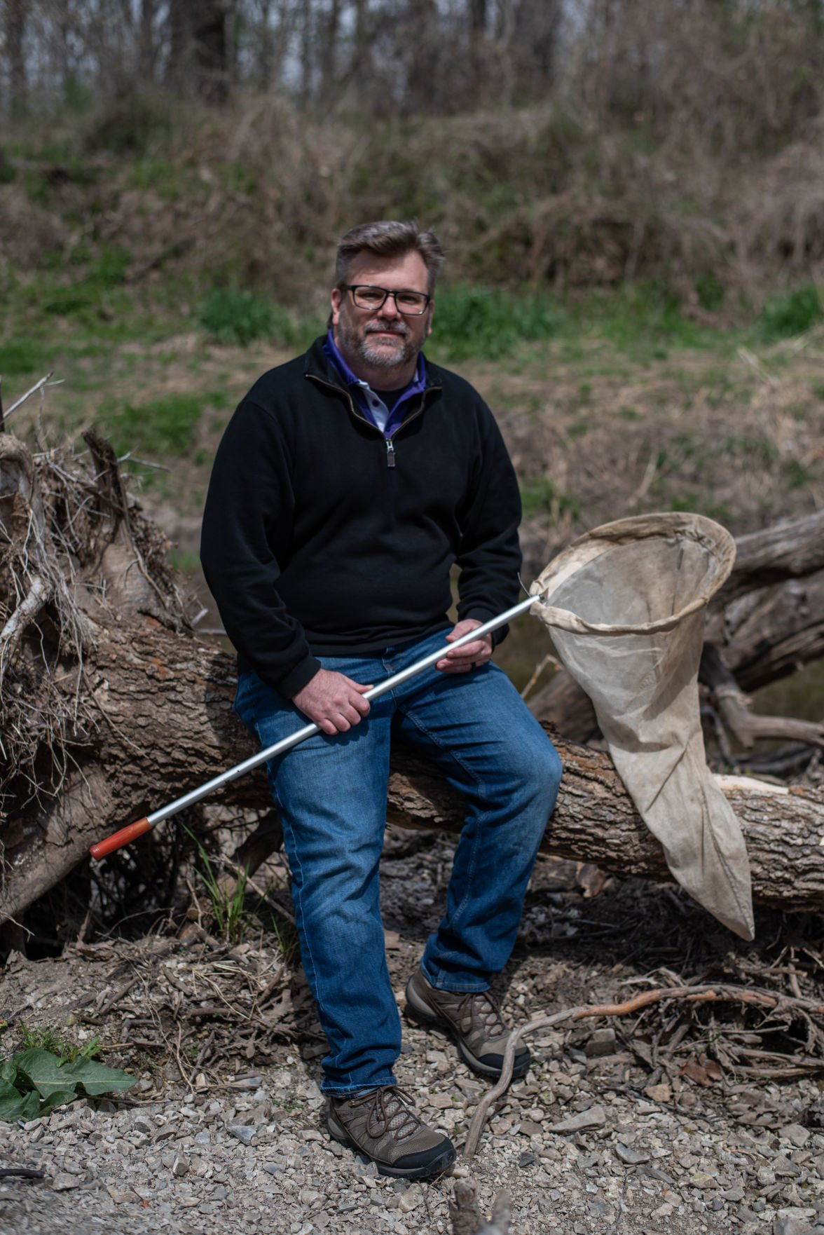 Jeremy Marshall, Entomology Professor at K-State, holds his insect sweep net while sitting on a log in the creek behind Wildcat Park on Saturday.