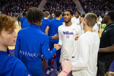 K-StateÕs Antonio Gordon (middle) and Pierson McAtee (right) meet the KansasÕ team at half court before playing against each other.