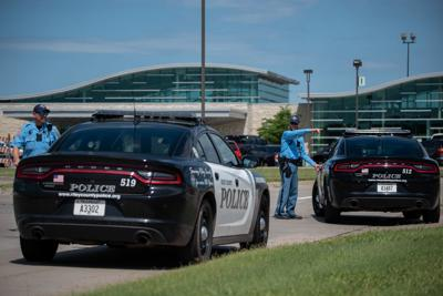 RCPD Officer Brian Jolley, right, points while talking to Sgt. Pat Tiede outside of Manhattan Regional Airport in response to a bomb threat on Friday afternoon.