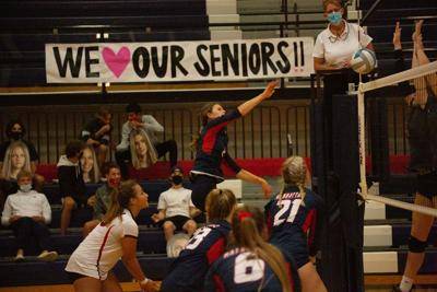 """(2) Monroe Say, a junior, spikes ball below sign that reads """"We love our seniors!!"""". The Manhattan High School Volleyball team played in a tournament with three opposing teams dominating with a final game score of 3-0."""