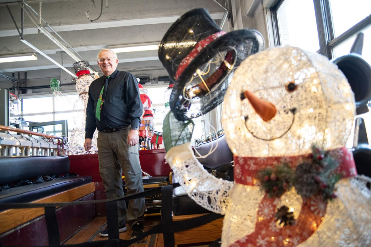 Wynn Butler stands on a retired firetruck that he decorated in Chritsmas lights with his wife in the garage at Manhattan Fire Station #2