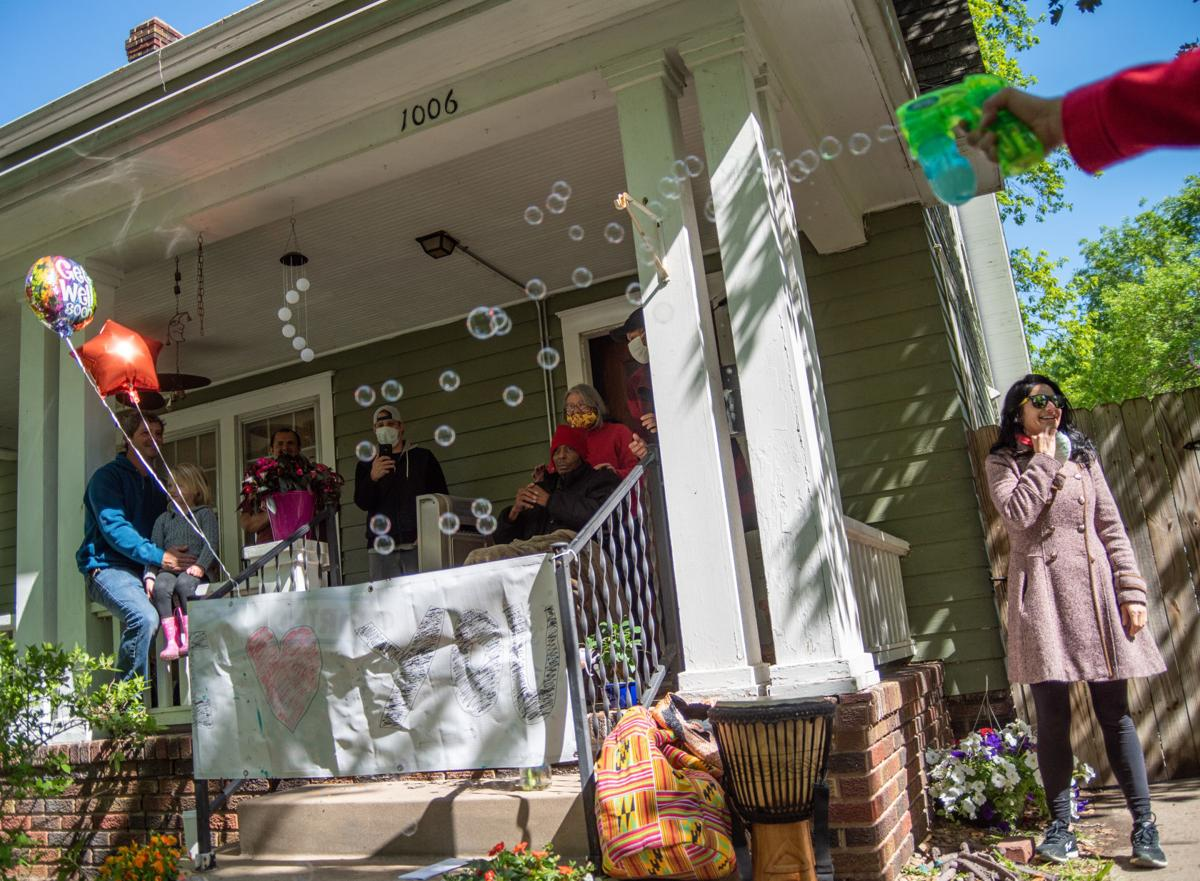 Diane Freeby blows bubbles in Richard PittsÕ front yard as Cindy Pitts and Richard Pitts (middle) look at everyone waving to Richard from Leavenworth Street on Friday.