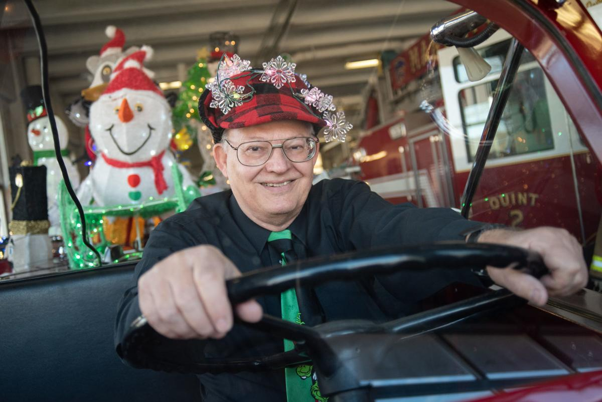 Wynn Butler sits in the driverÕs seat of a retired firetruck that he decorated in Chritsmas lights with his wife in the garage at Manhattan Fire Station #2