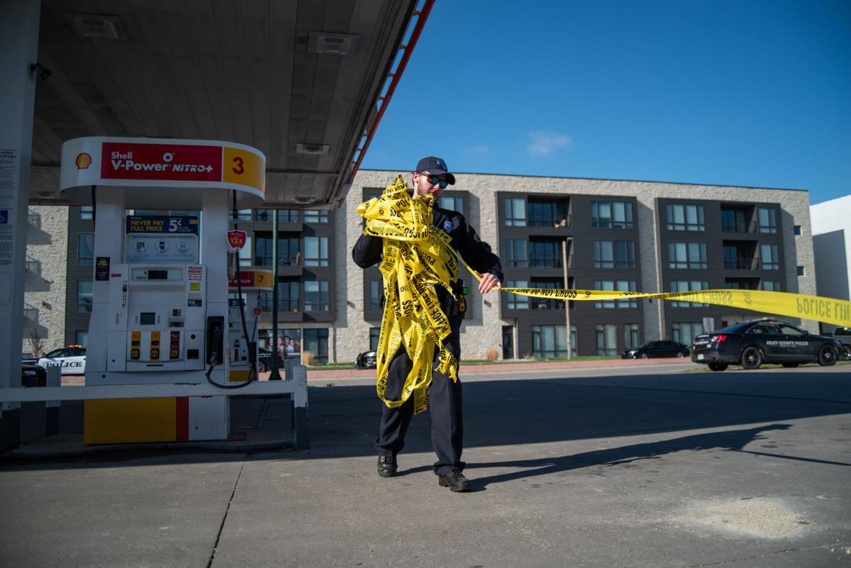 Riley County Police Officer Tracy takes down the police tape around the Shell gas station on Bluemont Avenue.