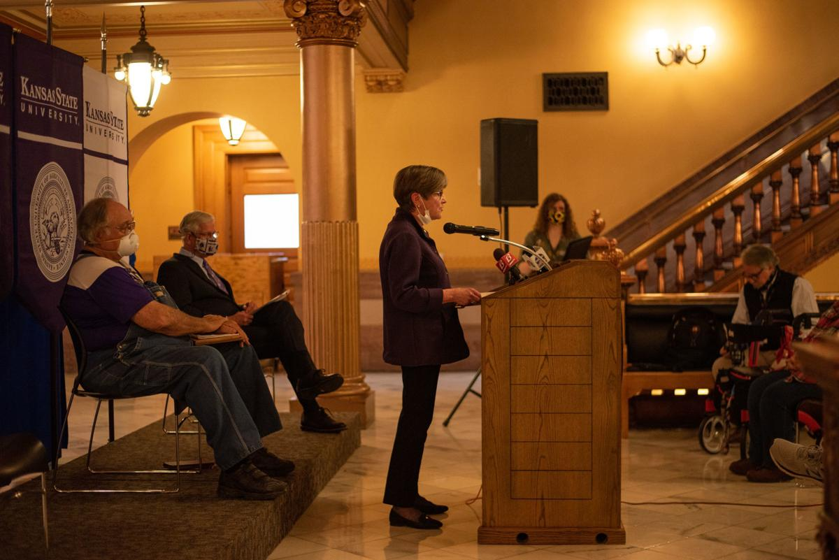 Governor Laura Kelly speaks in front of Dennis Ruhnke and K-State President Richard Myers at the Kansas State Capitol in Topeka.