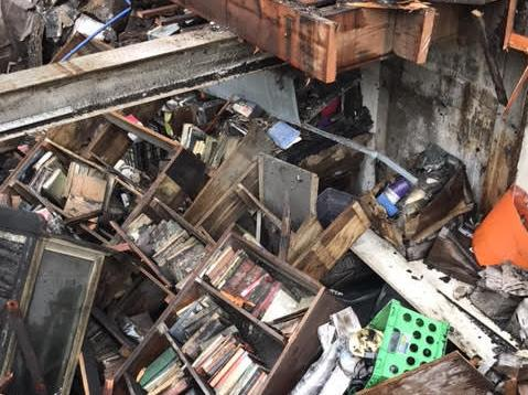 Books And Other Items Sit In The Basement Of Dusty Bookshelf After Workers Pulled Up Floor Recently To Clear It Out Building Was Destroyed A