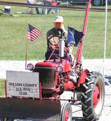 Charlie Lewis, Old Iron Club member, rides on his tractor.
