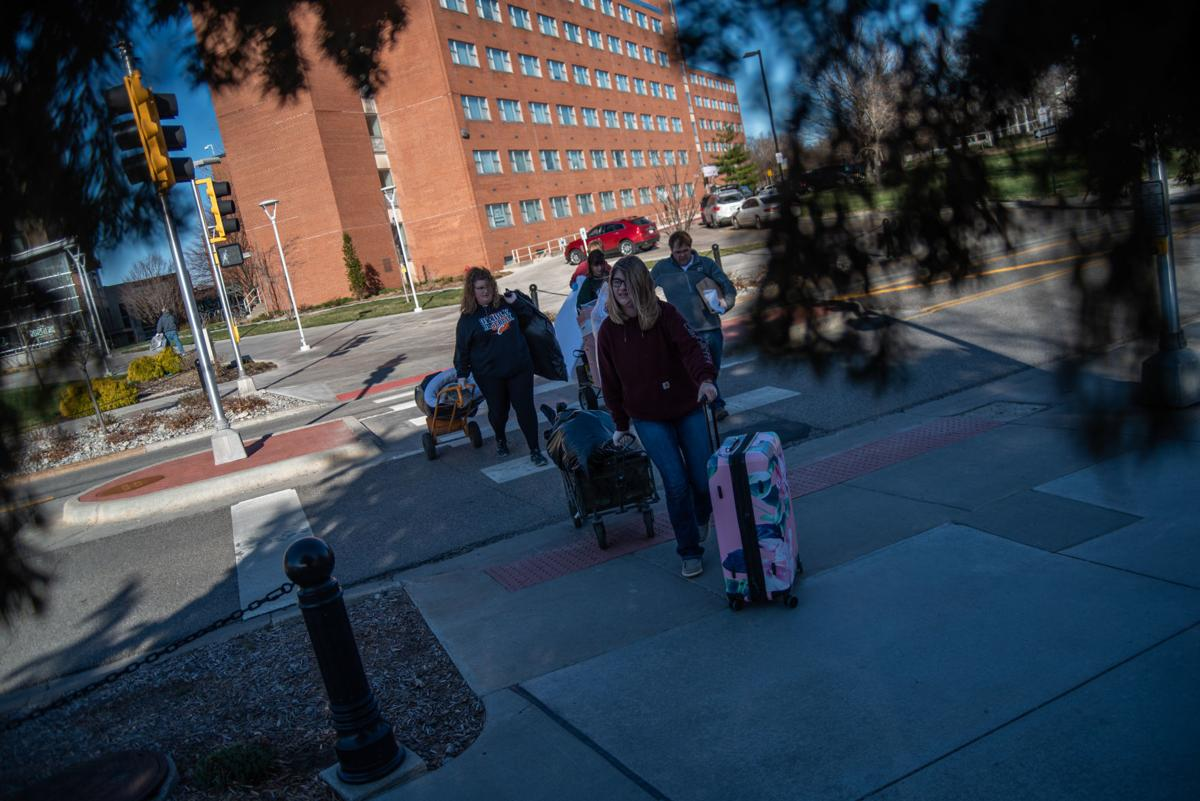 Krista Rehkop, right, and Kelsie Rehkop, middle, walk out of Wefald Hall with Katie RehkopÕs belongings during her move-out slot on Friday.