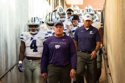 Kansas State head coach Chris Klieman is followed by his team