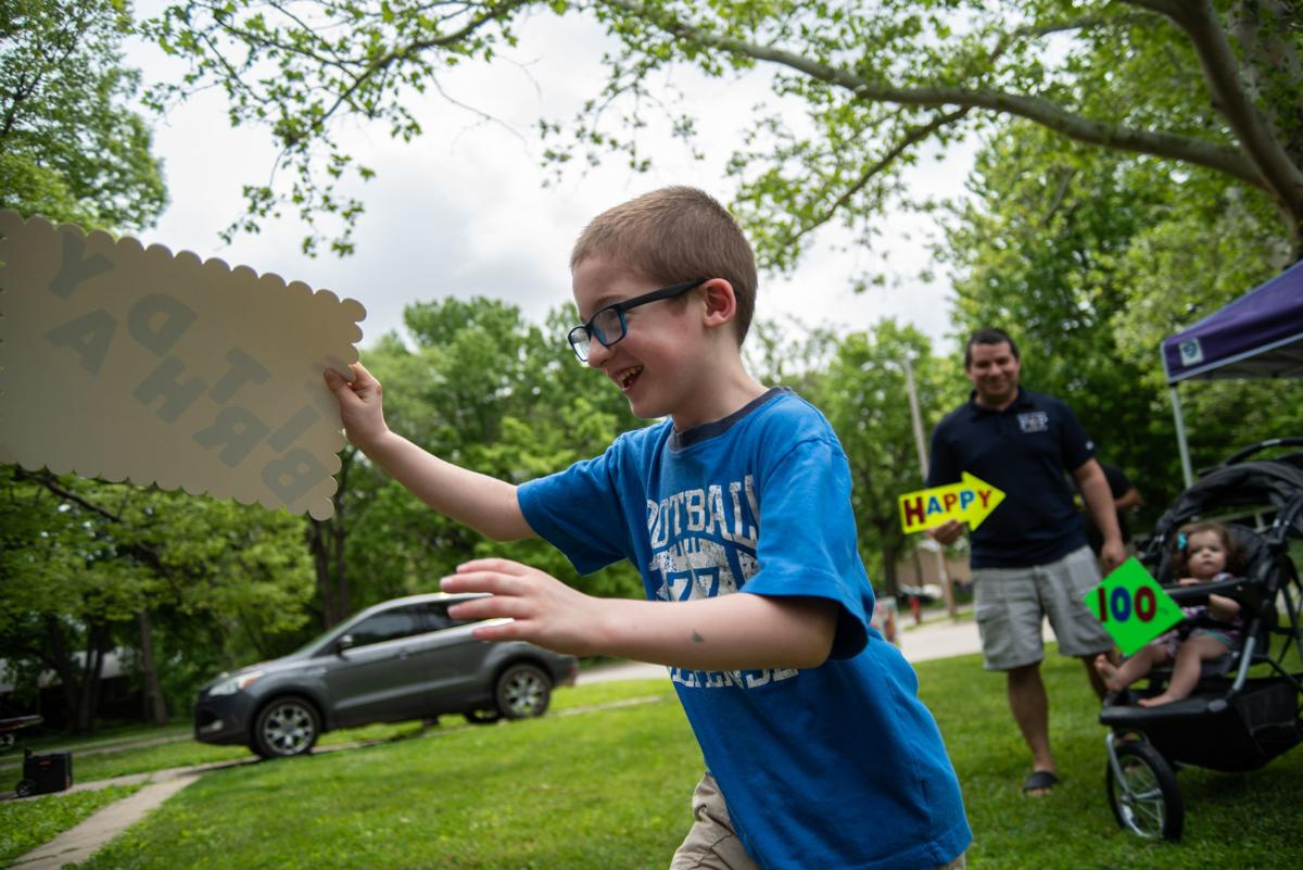 Samuel Beaubien, 6, runs through the front yard to give Carrol Joy a sign on JoyÕs 100th birthday on Saturday.